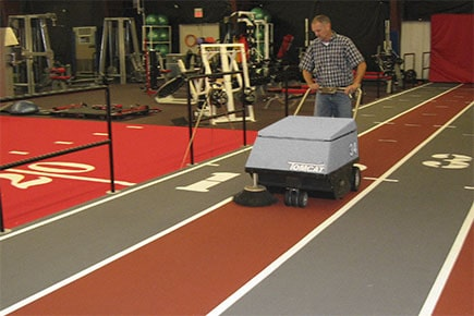 Sweeping a sporting facility with a Model 34 battery powered sweeper