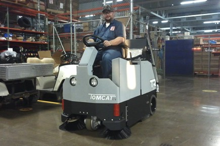Fast factory floor sweeping with a battery powered ride-on floor sweeper